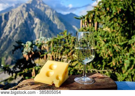 Glass Of Swiss Or Savoy Dry White Wine And Yellow Emmental Cheese With Alpine Mountains Peaks On Bac