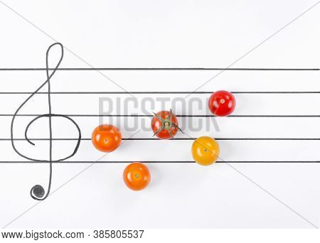 Multicolored Cherry Tomatoes On The Musical Staff. Creative Food Background. Symphony Of Flavors