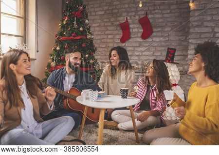 Friends Celebrating Christmas At Home, Eating Christmas Cookies, Drinking Coffee, Playing The Guitar