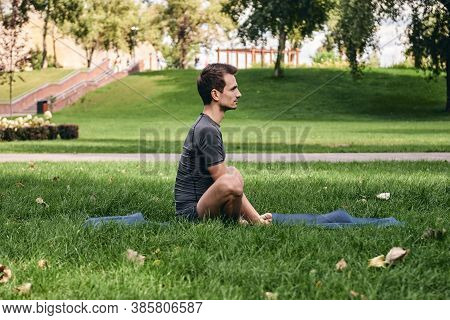 Young Man In Sportswear Doing Yoga In The Park. Practice Asana Outdoors. Exercising On Green Grass O
