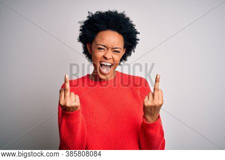 Young beautiful African American afro woman with curly hair wearing red casual sweater Showing middle finger doing fuck you bad expression, provocation and rude attitude. Screaming excited