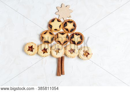 Christmas Homemade Mince Pies In Form Of Christmas Tree On White Cement Background
