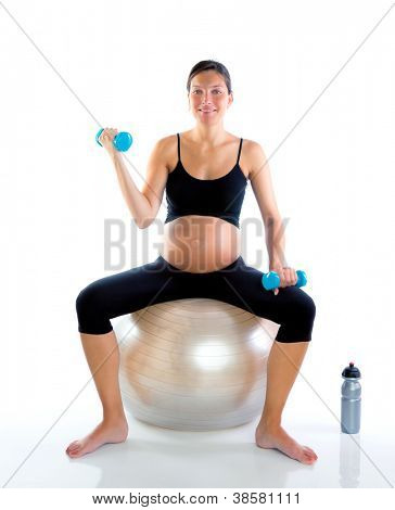Beautiful pregnant woman at fitness gym with dumbells on aerobics ball poster