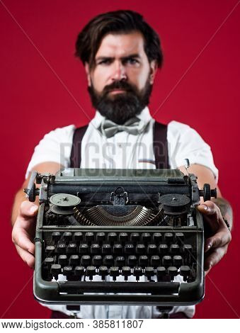 Bearded Man In Suspenders With Retro Typewriter. Brutal Guy In Bow Tie. Elegant Male Typist. Handsom