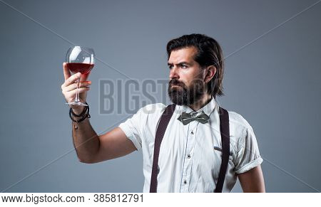 Trendy Man In Suspenders And Bow Tie With Wine. Confident Elegant Man Drinking Wine From Glass. Alco