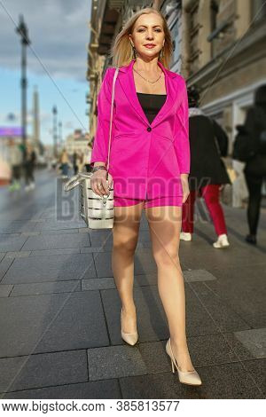 Mature Attractive Business Woman In Pink Suit Is Walking On The Street Of The City At The Daytime.