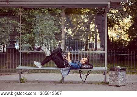 Young Man With Laptop On His Knees Is Lying On The Public Transport Station While Waiting For A Bus.