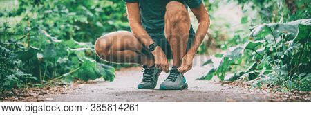 Sports watch athlete tying running shoes getting ready to run with smartwatch. Fitness runner jogging in spring autumn jogging outdoor wearing technology wearable smart watch. Banner.