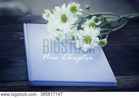 Inspirational Motivational Words - New Chapter. Written On A Blue Book Cover With White Daisy  Flowe