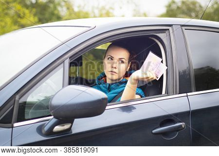 Serious Woman Holding Out Drivers License And Car Documents, Driving Her Car. Traffic Violation Conc