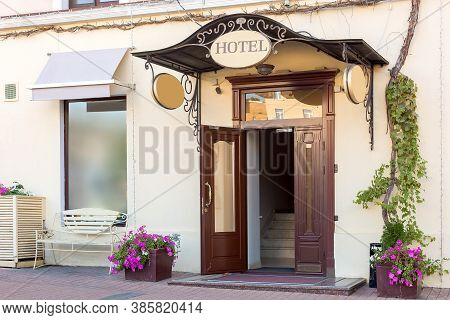 Entrance Door With A Threshold And A Visor With A Hotel Sign On The Facade Of The Building With A Fl