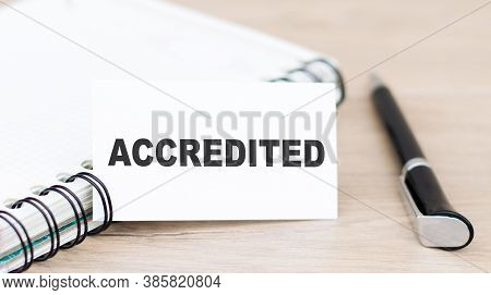 Card With Accredited Text On Green Wooden Background Next To Notepad And Pen