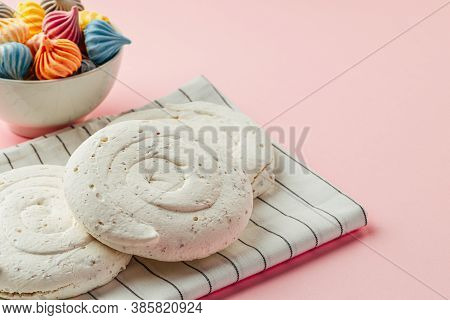 White Meringue Cookie On Pink Background With Colorful Mini Meringues