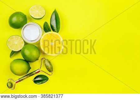 Bright Summer Citrus Flatlay With Face Moisturizer, Jade Roller Massager, Lemons And Limes Isolated