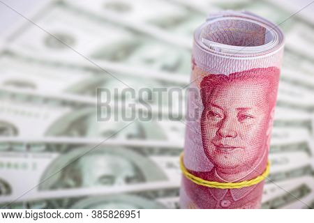 Roll Of One Hundred Reais Bills, With 100 Yuan Notes In The Blurred Background. Chinese Market Valua