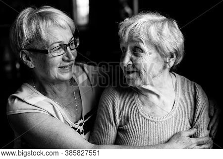 Happy old woman with her adult daughter. Black and white photo.