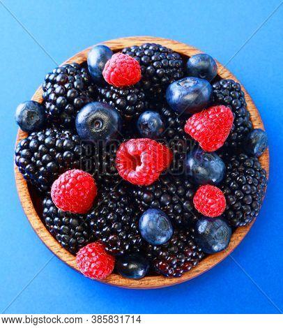 Bowl of fresh fruit. Blackberries,raspberries,blueberries on a bowl over blue background. Healthy breakfast. Vegan sweet food.
