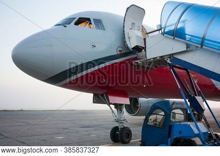 Front Of The Passenger Airplane With Open Door And Jetway Ramp Near
