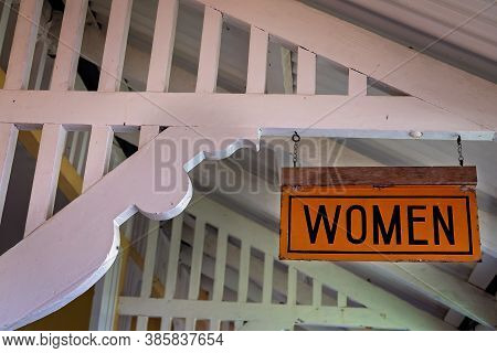 A Vintage Sign Indicating Washroom Fro Women Hanging From Rafters Of Retro House