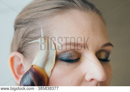 Model Holds Snail On Face. Ads For Cosmetics, Anti-gravity Creams, Lip Treatments, Face Treatments,