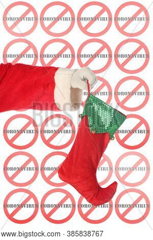 Santa Claus holds a Christmas Stocking. Santa Claus arm holds a Red and Green Christmas Stocking in the air with an International NO CORONAVIRUS repeating logo in the background. Covid 19 is dangerous