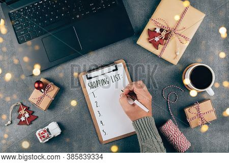 Christmas Online Shopping Flat Lay. Girl Writing Shopping List. Laptop, Present Box, Cup Of Coffee,