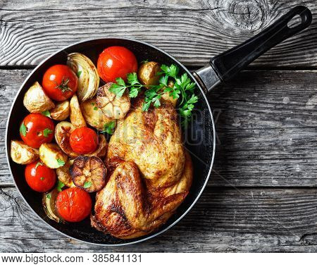 Half Of Roast Chicken In A Skillet With Roasted Potato, Fresh Tomatoes, Peppers And Herbs On A Rusti