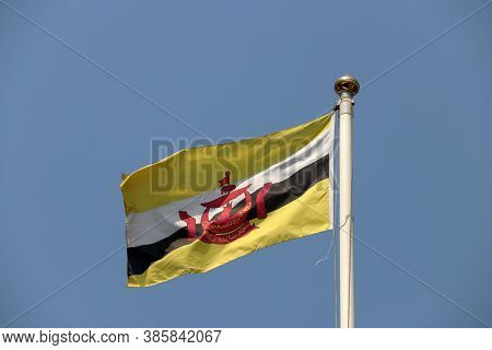 National Flag Of Brunei On Bright Blue Sky Background. Blown Away By Wind. Brunei Is One Of The Ten