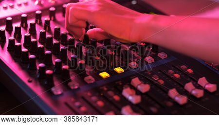 Close Up Of Asian Hand Producer Working At Mixing Panel In The Boutique Recording Studio. Modern Mus