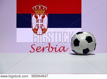 Small Football On The White Floor And Serbian Nation Flag With The Text Of Serbia Background. The Co