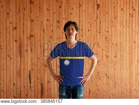 Man Wearing Nauru Flag Color Shirt And Standing With Akimbo On The Wooden Wall Background, A Blue Fi