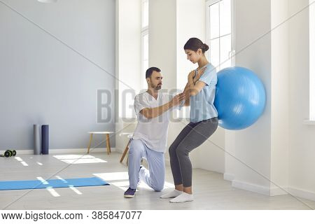 Physiotherapist Helping Young Woman Recover From Back Injury Using Big Soft Ball