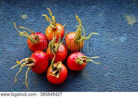 Appetizing Yellow-red Rose Hips On Lie On A Dark Background