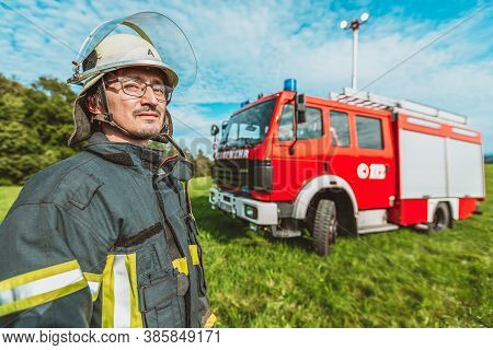 A German Fireman Stands Near A Firetruck