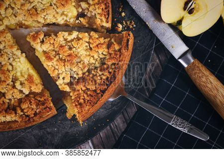 Slice Of Traditional European Apple Pie With Topping Crumbles On Cake Server Surrounded By Fresh App