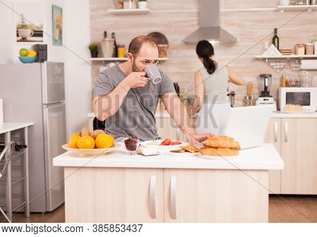 Freelancer Drinking Coffee And Working From Home While His Wife Prepares The Breakfast. Freelancer W