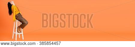 Horizontal Concept Of Trendy Woman In Autumn Outfit Sitting On White Stool And Looking Up On Orange