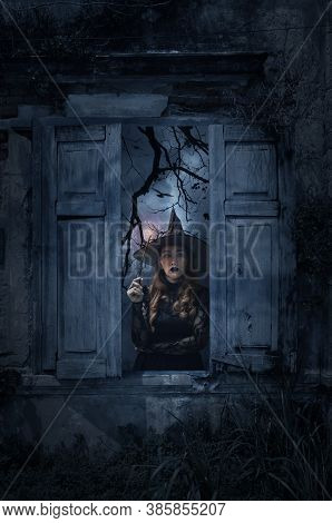 Halloween Witch Holding Magic Wand Standing In Old Damaged Wood Window With Wall Over Cross, Church,