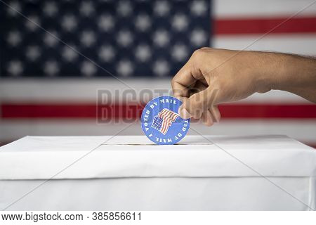 Close Up Of Hands Dropping I Voted My Mail Stickers Inside The Ballot Box With Us Flag As Background