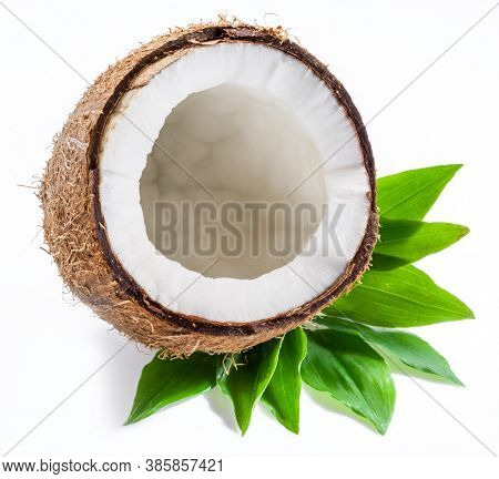 Cracked coconut half with white flesh over green leaves isolated on white background.