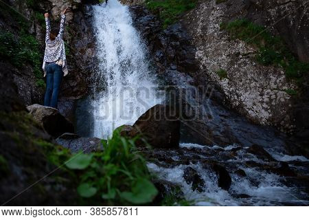 Young Happy Woman Enjoing The Waterfall. Woman Standing In Front Of Waterfall With Rased Hands And S