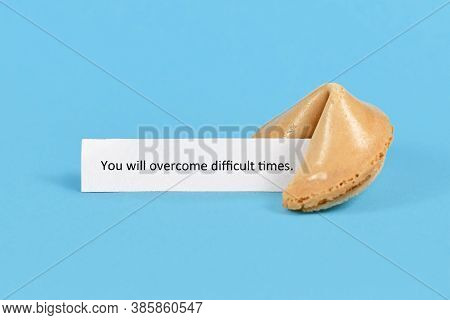 Fortune Cookie With Motivational Text On Paper Saying 'you Will Overcome Difficult Times' On Blue Ba