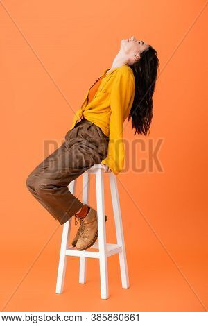 Trendy Woman In Autumn Outfit Sitting On White Stool And Looking Up On Orange