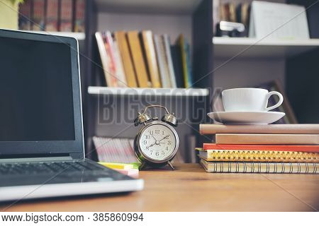 Laptop And Book On School Table For Student Study For Exam In Library. Wooden Desk With Desktop Lapt