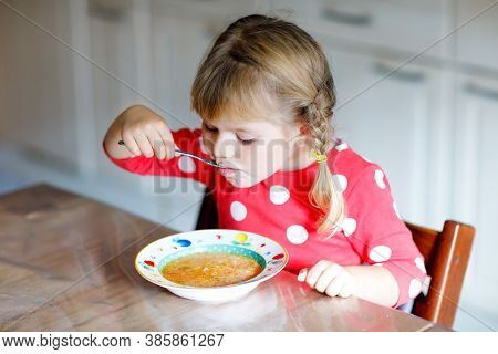 Adorable Little Toddler Girl Eating Fresh Cooked Vegetable Soup In Kitchen. Happy Child Eats Healthy