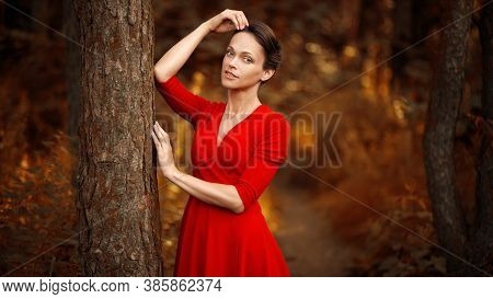 Pretty Young Woman Is Wearing A Red Dress In The Autumn Forest
