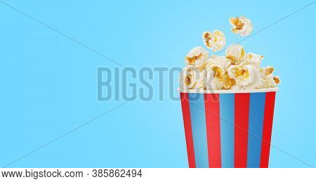 Popcorn In A Striped Cup Over Blue Background