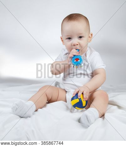 Photo Of A Ten-month-old Baby With Rattle And Ball