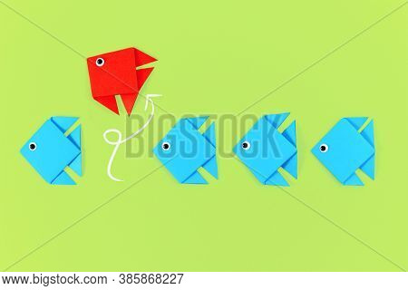 Red Paper Fish Swimming Out Of Line Of Blue Fish. Concept For New Business Strategies, Discovery, An