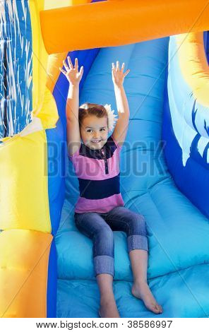 Little Girl sliding down an inflatable Slide